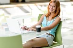 Muchacha del estudiante que se sienta en la sonrisa de la nave de montaje Fotografía de archivo