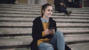 Muchacha del estudiante que se sienta por la tarde en la escalera y que mira alguien, sonrisa El smartphone del uso de la mujer,  metrajes