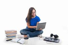 Muchacha del estudiante que se sienta sosteniendo el ordenador portátil con los libros alrededor Foto de archivo libre de regalías