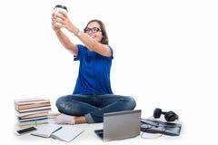 Muchacha del estudiante que sostiene el café alrededor de los libros y del teléfono Fotografía de archivo