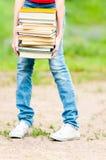 Muchacha del estudiante que sostiene la pila grande de libros pesados Imágenes de archivo libres de regalías