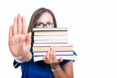 Muchacha del estudiante que sostiene los libros que muestran la cara de la cubierta de la parada Imagen de archivo libre de regalías