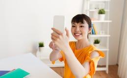 Muchacha del estudiante que toma el selfie por smartphone en casa Fotos de archivo