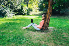 Muchacha del estudiante que trabaja con un ordenador portátil en un parque verde Fotografía de archivo