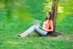 Muchacha del estudiante que trabaja con un ordenador portátil en un parque verde Imagen de archivo libre de regalías