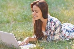 Muchacha del estudiante que trabaja en el ordenador portátil que miente en hierba en parque Fotografía de archivo
