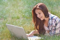 Muchacha del estudiante que trabaja en el ordenador portátil que miente en hierba en parque Fotos de archivo libres de regalías