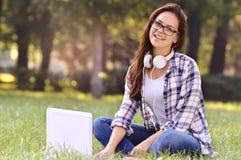 Muchacha del estudiante que trabaja en el ordenador portátil, sentándose en hierba en parque Foto de archivo libre de regalías