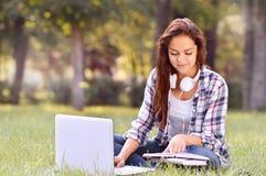 Muchacha del estudiante que trabaja en el ordenador portátil, sentándose en hierba en parque Imagen de archivo libre de regalías