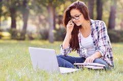 Muchacha del estudiante que trabaja en el ordenador portátil, sentándose en hierba en parque Fotos de archivo