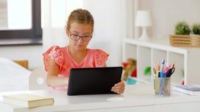 Muchacha del estudiante que usa la tableta en casa metrajes
