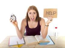 Muchacha del estudiante universitario en la tensión que pide la ayuda que celebra concepto del examen del tiempo del despertador Fotos de archivo
