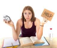 Muchacha del estudiante universitario en la tensión que pide la ayuda que celebra concepto del examen del tiempo del despertador Imagenes de archivo