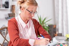 Muchacha del estudiante universitario que hace la preparación en su escritorio Imagen de archivo