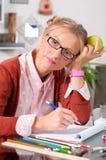 Muchacha del estudiante universitario que hace la preparación en su escritorio Fotos de archivo