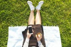 Muchacha del estudiante universitario que se sienta en la mensajería verde del césped que manda un SMS en su dispositivo del smar Fotografía de archivo