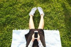 Muchacha del estudiante universitario que se sienta en la mensajería verde del césped que manda un SMS en su dispositivo del smar Fotos de archivo libres de regalías
