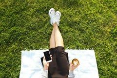 Muchacha del estudiante universitario que se sienta en la mensajería verde del césped que manda un SMS en su dispositivo del smar Fotos de archivo
