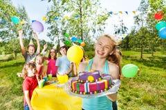 Muchacha del feliz cumpleaños que sostiene la torta de formación de hielo de la masilla Foto de archivo libre de regalías