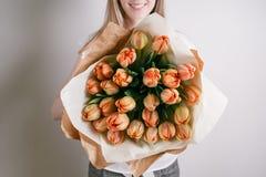 Muchacha del florista con las flores de la peonía o ramo anaranjado de la flor de la mujer joven de los tulipanes para el día de  Imagen de archivo