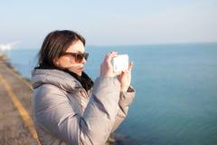 Muchacha del fotógrafo en la playa Foto de archivo