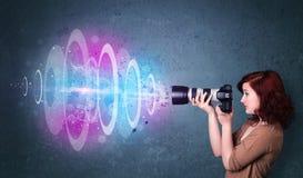 Muchacha del fotógrafo que hace las fotos con el haz luminoso potente Foto de archivo libre de regalías
