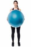 Muchacha del gimnasio que presenta una bola suiza Fotos de archivo