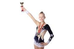 Muchacha del gimnasta con la taza de oro y las medallas Imagenes de archivo