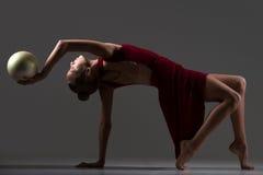 Muchacha del gimnasta que hace ejercicio del puente con la bola Imagen de archivo libre de regalías