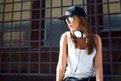 Muchacha del golpeador con los auriculares en una ciudad europea Foto de archivo libre de regalías