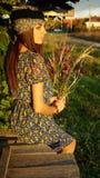 Muchacha del granjero con las flores salvajes en un pueblo Foto de archivo