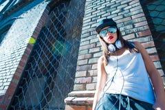 Muchacha del hip-hop con los auriculares en un ambiente urbano Fotografía de archivo libre de regalías