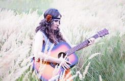 Muchacha del hippie con la guitarra que camina en un prado Foto de archivo libre de regalías
