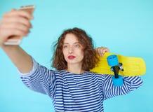 Muchacha del inconformista con el monopatín que hace el selfie Fotos de archivo