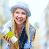 Muchacha del inconformista con la taza de bebida caliente en la calle de la ciudad Imagenes de archivo