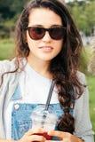 Muchacha del inconformista con las gafas de sol que bebe un smoothie Fotos de archivo