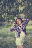 Muchacha del inconformista con los auriculares que bailan debajo de árbol Fotos de archivo libres de regalías