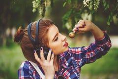 Muchacha del inconformista con los auriculares y la piruleta Fotos de archivo