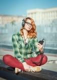 Muchacha del inconformista con música que escucha de los auriculares Fotografía de archivo libre de regalías