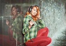 Muchacha del inconformista con música que escucha de los auriculares Foto de archivo