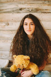 Muchacha del inconformista con un juguete del oso en un fondo de madera Fotografía de archivo