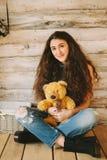 Muchacha del inconformista con un juguete del oso en un fondo de madera Imagen de archivo libre de regalías