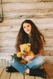 Muchacha del inconformista con un juguete del oso en un fondo de madera Fotos de archivo