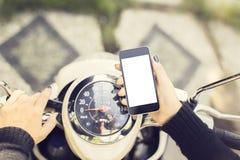 Muchacha del inconformista con un teléfono en blanco y una moto Fotos de archivo