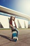 Muchacha del inconformista de la moda en gafas de sol con el monopatín Fotos de archivo
