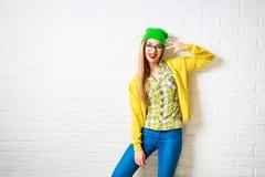 Muchacha del inconformista de la moda en la pared de ladrillo blanca Foto de archivo libre de regalías