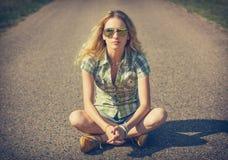Muchacha del inconformista del estilo de la calle que se sienta en el camino Imagen de archivo libre de regalías