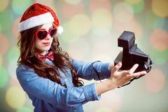 Muchacha del inconformista en el sombrero de Papá Noel que hace el selfie con retro Fotografía de archivo libre de regalías