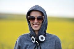 Muchacha del inconformista en sudadera con capucha, gafas de sol y auriculares en el al aire libre Fotos de archivo