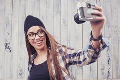 Muchacha del inconformista en vidrios con la cámara del vintage Fotos de archivo